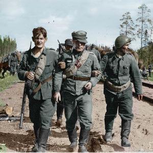 Sårade soldater går i armkrok längs ett järnvägsspår.