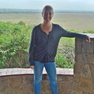 Marissa Gripenberg framför ett vidsträckt landskap i Kenya. Bakom hennes syns träd och gräs.