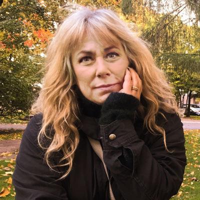 Stina Wollter lutar mot en gravsten i en höstig park i Helsingfors.