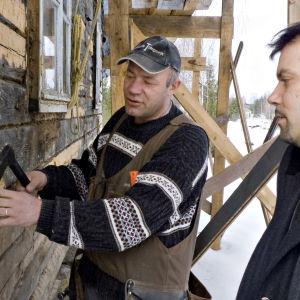 Haminalainen kirvesmies Tapani Marjanen (vas.) näyttää juontaja Jarkko Purolle, kuinka talo kengitetään eli vaihdetaan huonokuntoisia hirsiä jopa keskeltä seinää.