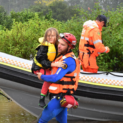 En man bär iland ett barn från en båt.
