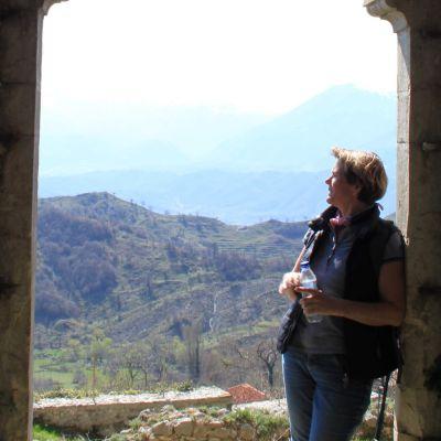 En kvinna står vid en port och blickar ut över närbelägna berg och dalar.