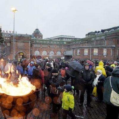 Ihmisiä sateessa ja tuiskussa Veikko ja Lahja Hurstin Laupeudentyö ry:n perinteisessä itsenäisyyspäivän linnanjuhlassa Hakaniementorilla Helsingissä 6. joulukuuta.