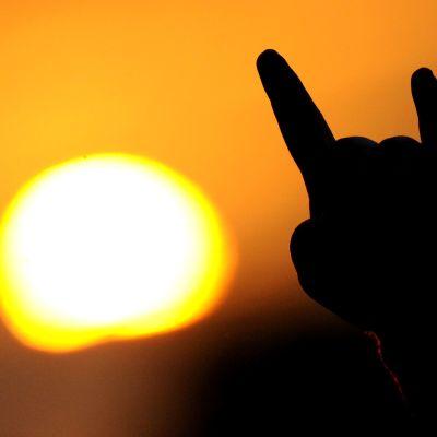 Hand i luften mot en nedåtgående sol.