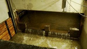 Vatten rinner och träluckan syns