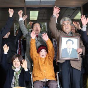Kim Sung-joo ihmisjoukon keskellä. Kaikilla on kädet ilmassa.