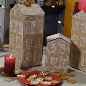 Tre miniatyrhus byggda av brun kartong, dekorerade med vit tusch. Framför husen står ett fat med pepparkakor och ett ljus som brinner.