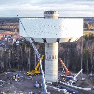 Ett vattentorn i vidbild. På marken sysn flera bilar och maskiner som ser ut att jobba med att bygga tornet.