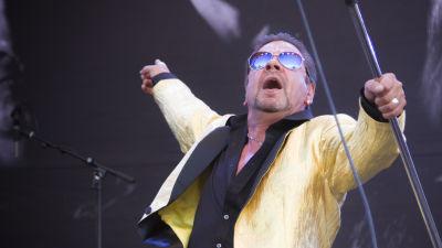 Mies esiintymislavalla mikrofoninjalka kädessä.