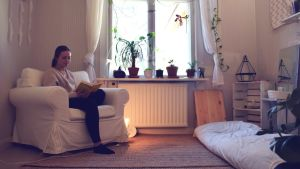 Cecilia Weckström sitter i en vit fotölj och läser bok i sitt ljusa och lilla rum.