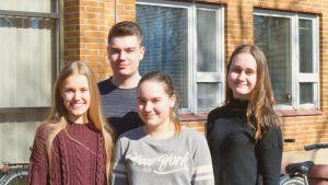 Fyra gymnasieelever ståt ute på en skolgård.