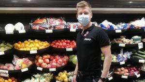 Mansperson står med munskydd på och tittar in i kameran. I bakgrunden fruktkorgar på rad i butikshylla.