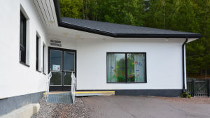 En vit byggnad med svarta detaljer. Ovanför ingången står det hälsogård terveystalo.