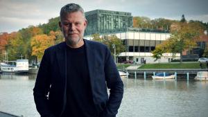 Arne Dahl/Jan Arnald står framför finska teatern vid Aura Å. Träden har en sprakande höstgul färg.
