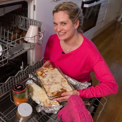 Tuulianna Tola astianpesukoneen ääressä, kädessään lasagne.