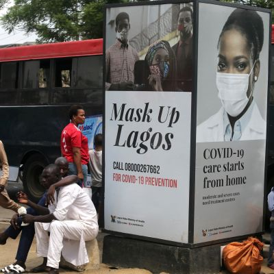 """Ihmisiä istui bussipysäkillä Lagosissa kyltin edessä, jossa luki """"mask up Lagos""""."""