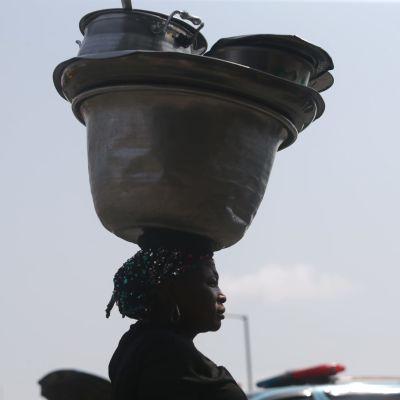 En kvinna som säljer mat på gator i Lagos, Nigeria, bar på sina kärl där den 9 mars.