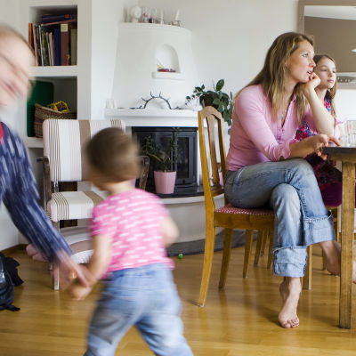 Äiti ja lapsia kotona kahvipöydässä, pikkulapset juoksevat lattialla.