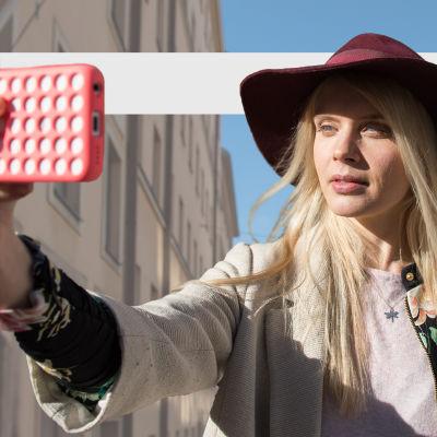 Donna (Alina Tomnikov) pitää kadulla ojennetussa kädessään puhelinta itseään päin. Taustalla kerrostalot.