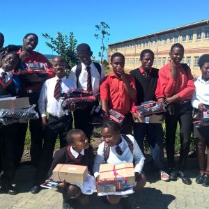 Skolelever i Sydafrika i skoldräkter, i bakgrunden skymtar en tvåvåningsbyggnad i gult tegel. De 15 eleverna har gåvor i famnen. Unga tonåringar.