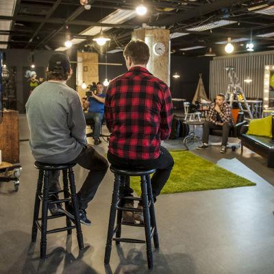 Studio, kaksi ihmistä istuu tuoleilla ja tv-kamera kuvaa heitä