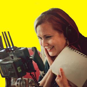 Anna Dahlman katsoo nauraen monitoriin keltaisessa kuvassa.