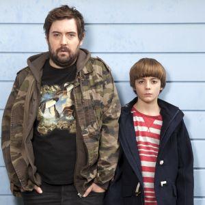 Mies ja poika seisovat seinää vasten ja katsovat kameraan.