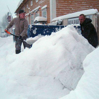 Två män skottar snö