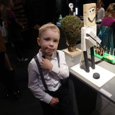 Kuvassa poika ja puuveistos.