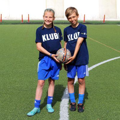 11-vuotiaat jalkapalloilijat Aada Mäkelä ja Oliver Berg harjoituskentällä.