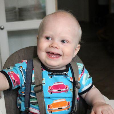 Vuoden ikäinen lapsi istuu hymyillen syöttötuolissa.