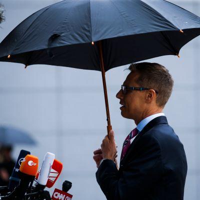 Sivusta otettu valokuva Alexander Stubbista sateenvarjon alla.