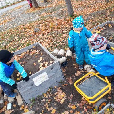 Lapsia istutuslaatikoiden keskellä.