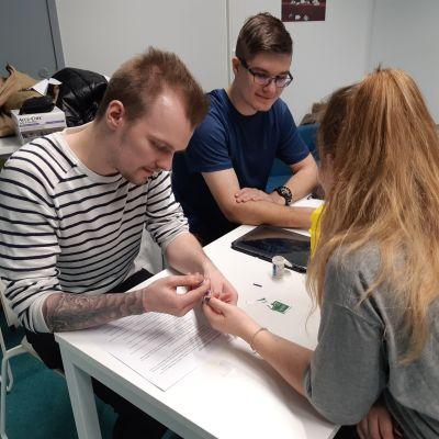 Kolme sairanhoitaopiskelijaa mittaavat toisiltaan verensokeria.