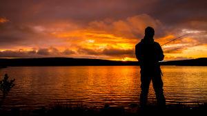 Kalastaja auringonlaskun aikaan