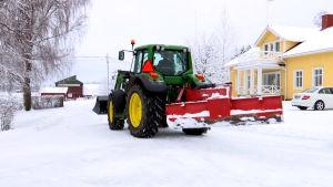 En traktor med plog i snöigt landskap.