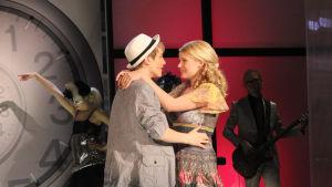 Vilma ja Jani syleilevät toisiaan. Takana tanssijoita ja bändiä.