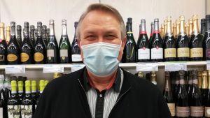 Mansperson med munskydd ser in i kameran. I bakgrunden vinflaskor på rad i butikshylla.