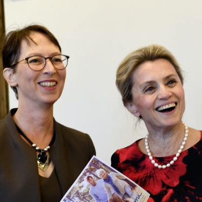 En leende Sari Essayah och en leende Päivi Räsänen, som håller i en broschyr, framför Kristdemokraternas logga.