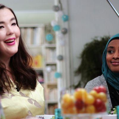 Ninja Sarasalo hymyilee, vieressä Maryan Abdulkarim katsoo Ninjaan päin hymyillen.