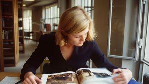 Flicka läser vid bord