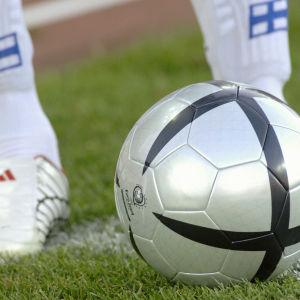 Suomen jalkapallomaajoukkueen pelaajan jalat ja pelipallo kentällä.