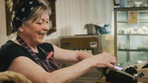 Porträtt på kvinna i svart t-skjorta och svart hårband. Hon sätter ny rulle med kvittopapper i sin kassa-apparat.