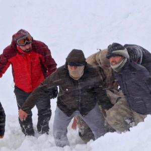 Personer går framåt i snön mitt i en snöstorm i Turkiet.
