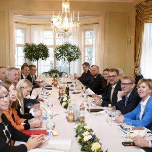 Representanter för alla partier sitter samlade i statsministerns tjänstebostad kring ett bord med vit duk och takkrona.