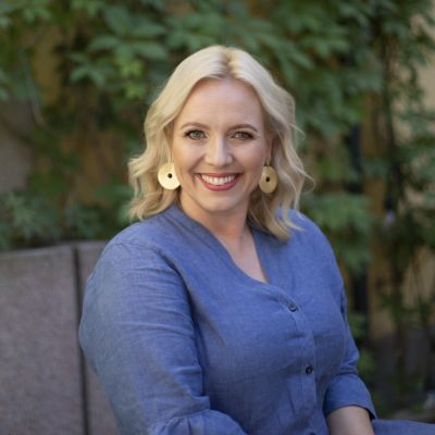 En kvinna med ljust hår och blå klänning ler in i kameran.