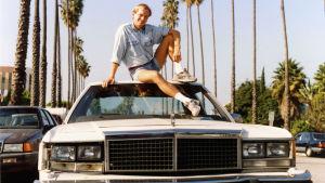 Dokumentaristen Michael Franck sitter på taket på en bil i Hollywood.