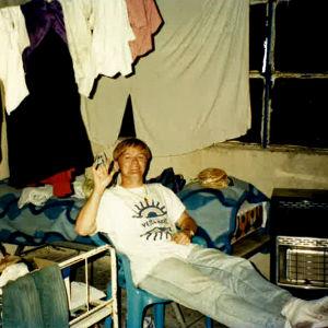 Nuori mies valkoisessa t-paidassa ja farkuissa istuu kahden hetekan välissä huoneessa jossa katosta roikkuu pyykkiä kuivumassa ja vaatteita on kasoina myös sängyillä.
