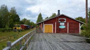 Till vänster tågspår och tågvagnar, till höger en röd träbyggnad med skylten Magasinboden.