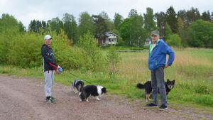 Två män och tre hundar står på en sandväg. Bakom dem syns träd och några hus.